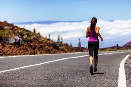žena v sportovém oblečení kráčí po ceste
