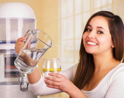 žena nalévá vodu s džbánu do poháře