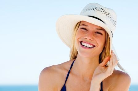 žena v plavkách, s kloboukem na hlavě se usmívá