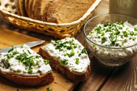 Domácí chléb s tvarohovou pomazánkou a zelenou bylinkou