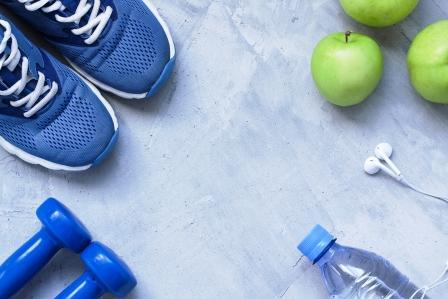 koncept zdravého životného stylu - tenisky, činky, voda a jabka