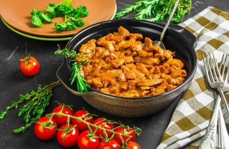 krútí maso nakrájené na kousky v pánvi - stroganov, paradajky a tymian