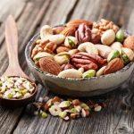 mix orechov v misce na dřevěném stole - vlašské, kešu, pistacie, lískové ořechy