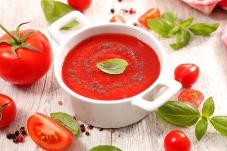 rajčatová polévka v bílé sklené misce - rajčata a bylinky na stole