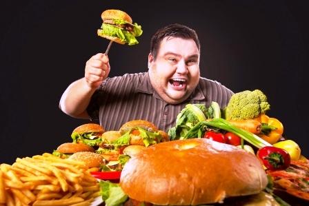 tucny muz si vybera medzi zdravym a nezdravym jidlom