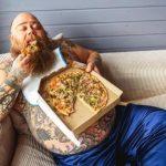 tuk na břichu. tlustý líný muž jí pizzu na gauči
