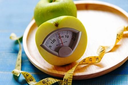 zelene jablko s hmotnostni stupnici a meraci paska